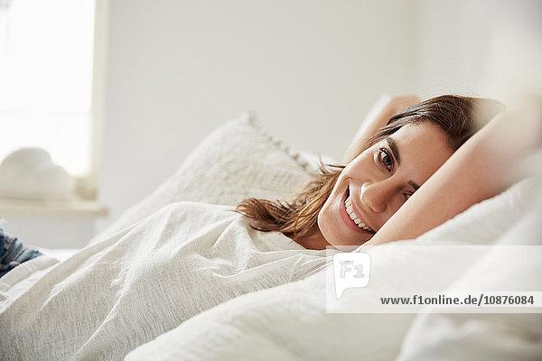 Porträt einer schönen jungen Frau auf dem Bett liegend