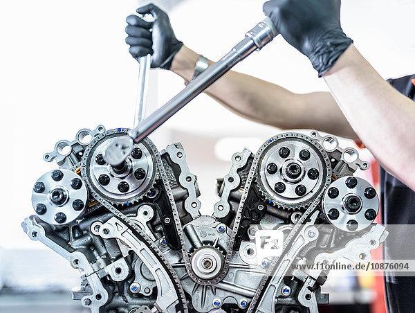 Ingenieur  der in einer Rennwagenfabrik an einem Motor arbeitet  Nahaufnahme