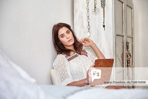 Porträt einer jungen Frau  die im Schlafzimmer sitzt und ein digitales Tablett benutzt