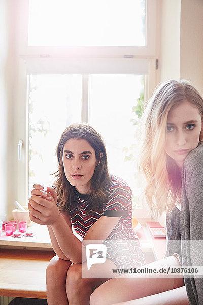 Porträt von zwei jungen Frauen  die auf dem Küchentisch sitzen