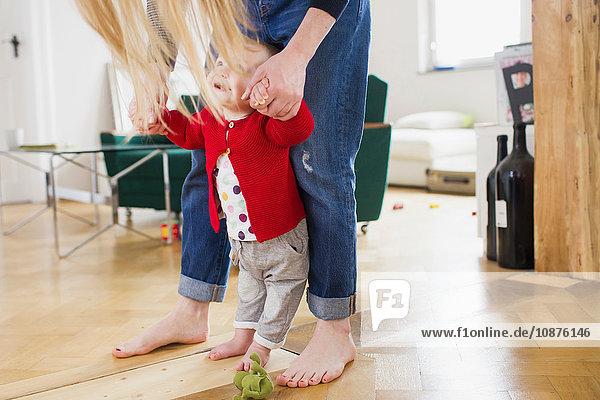 Kleines Mädchen hält Müttern die Hand und macht erste Schritte