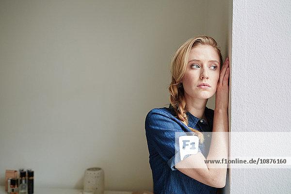 Hübsche junge Frau mit blondem Zopf  die an der Tür lehnt