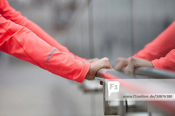 Hands of mature woman training  holding city handrail