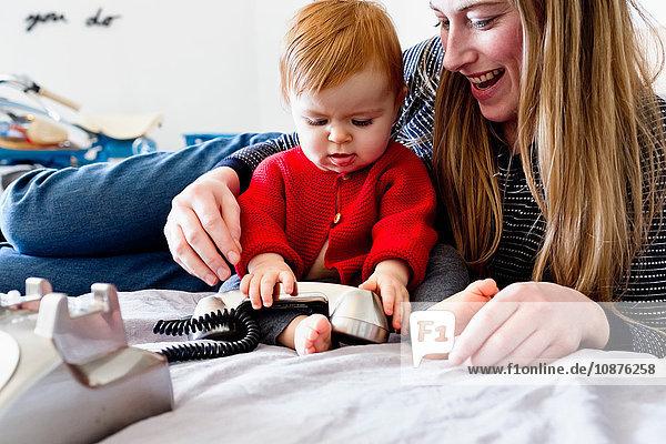 Mädchen und Mutter im Bett spielen mit dem Festnetztelefon
