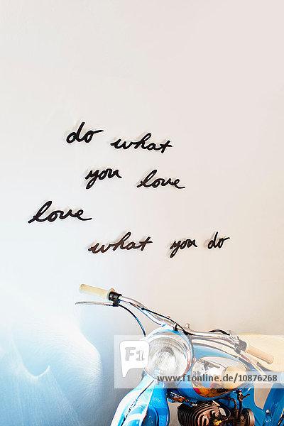 Hausinnenwand mit handgeschriebenem positivem Motto Design und Motorrad