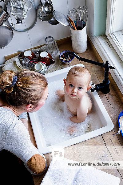 Portrait eines in der Küchenspüle badenden kleinen Jungen