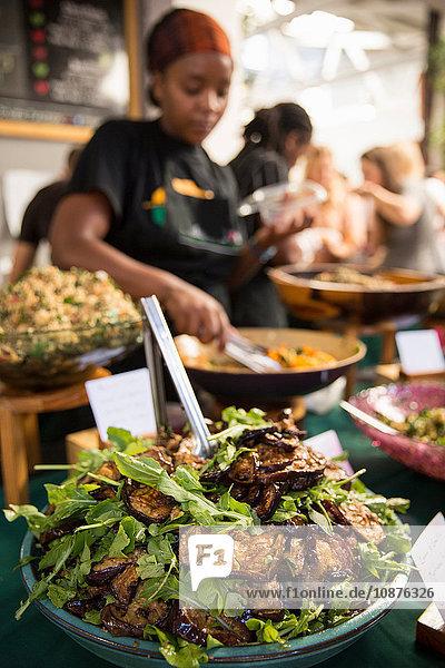 Stall holder serving eggplant salad at cooperative food market stall