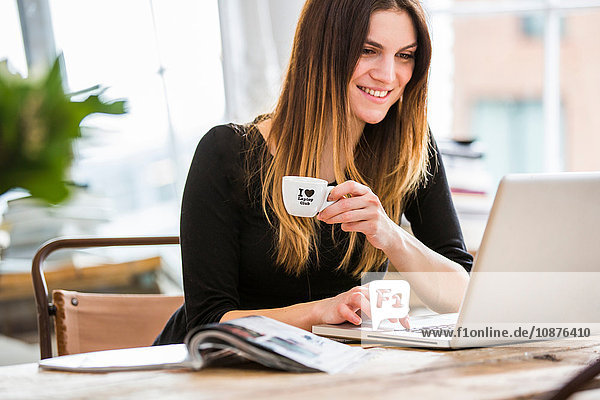 Young woman in city apartment drinking espresso whilst typing on laptop