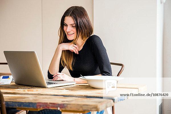 Junge Frau sitzt am Tisch in Wohnung mit Frühstück und liest Laptop