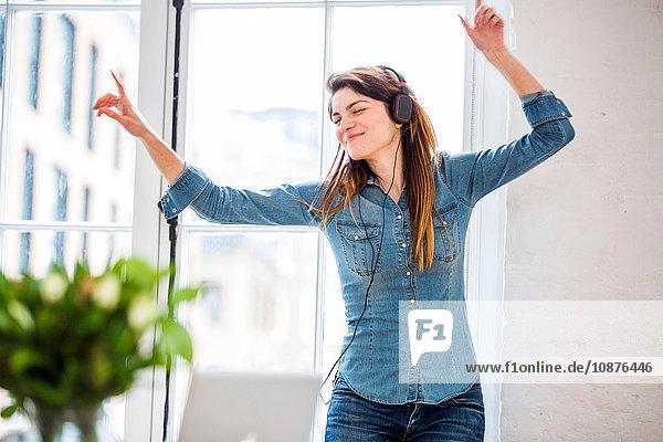Junge Frau mit geschlossenen Augen tanzt vor dem Fenster einer Stadtwohnung