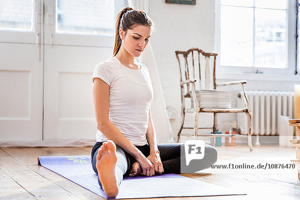 Young woman practicing yoga position in apartment