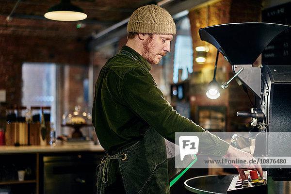 Männlicher Kaffeehausbesitzer mit Kaffeeröster