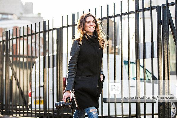 Junge Frau mit DSLR schlendert am Stadtzaun vorbei