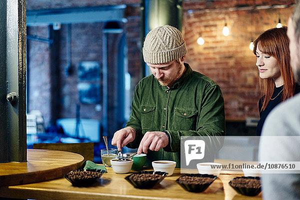 Coffee shop team preparing bowls of coffee and coffee beans at tasting