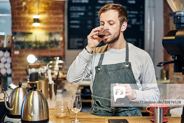 Male barista tasting coffee at coffee shop kitchen counter