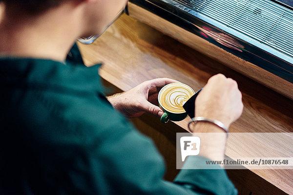 Über-Schulter-Ansicht eines männlichen Barista  der im Café Milch in eine Tasse gießt