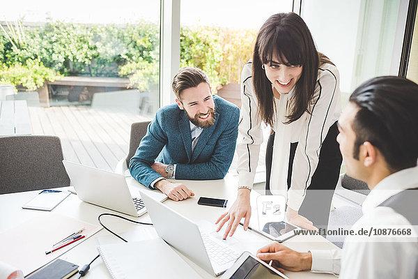 Junge Geschäftsfrau erklärt dem Team am Vorstandstisch