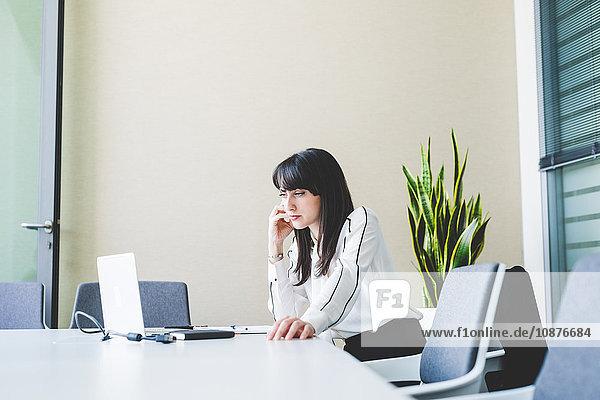 Geschäftsfrau starrt auf Laptop am Bürotisch