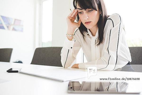 Gestresste junge Geschäftsfrau am Büroschreibtisch mit Notizblock