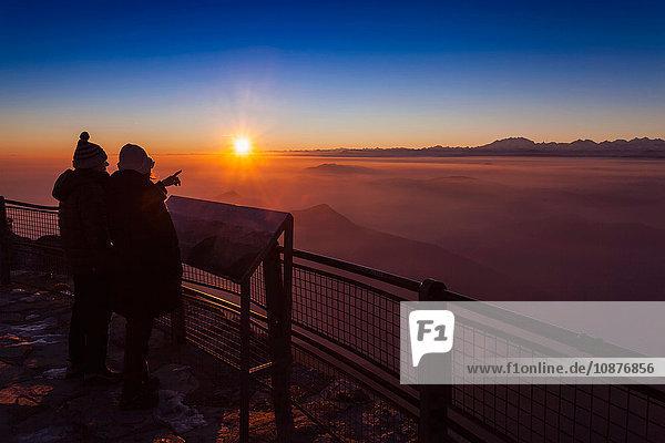 Senioren-Wanderpaar mit Blick auf den Nebel des Bergtals bei Sonnenuntergang  Monte Generoso  Tessin  Schweiz