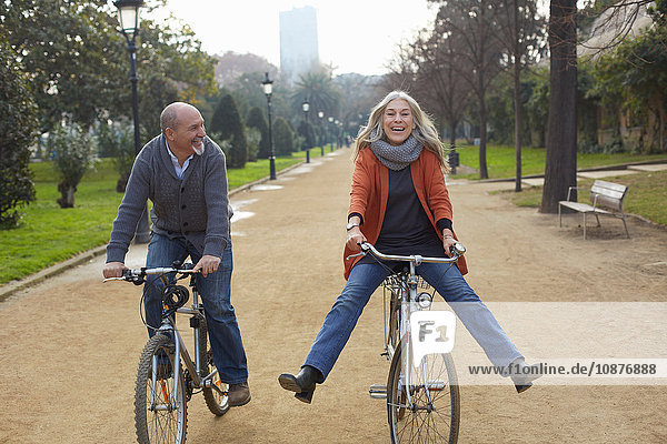 Couple riding bicycles on tree lined path in park  smiling