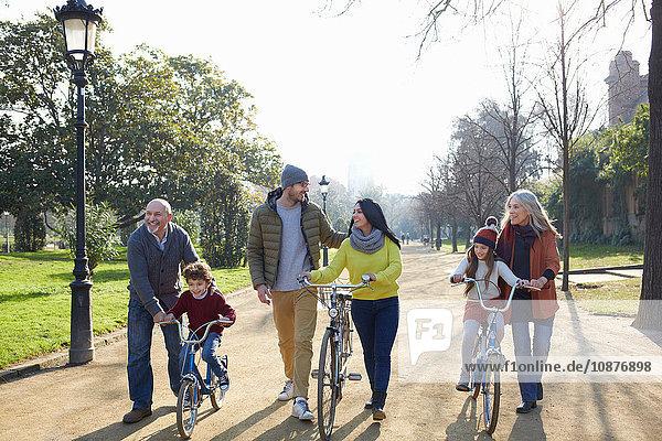 Mehrgenerationen-Familie im Park mit Fahrrädern