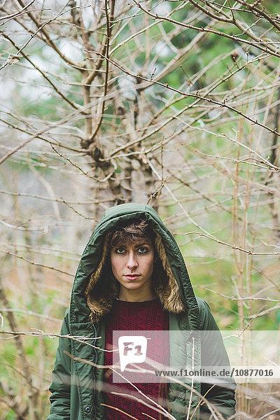 Porträt einer jungen Frau mit Kapuzenmantel im Freien