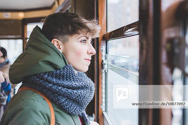 Junge Frau schaut aus dem Fenster der Seilbahn