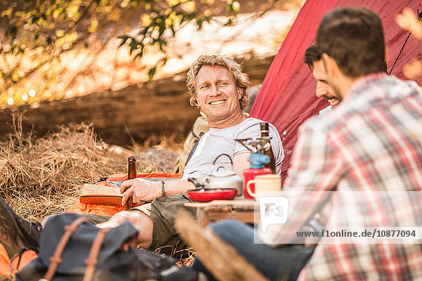 Men camping in forest drinking beer and coffee  Deer Park  Cape Town  South Africa