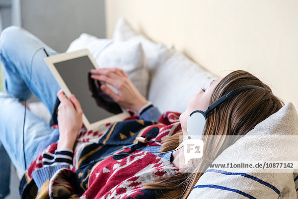 Blick über die Schulter einer Frau mit Kopfhörern und digitalem Tablett