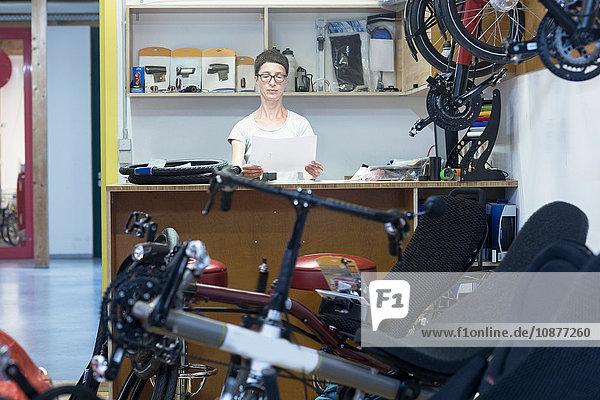 Frau in Fahrrad-Werkstatt hinter dem Tresen mit Blick auf den Papierkram