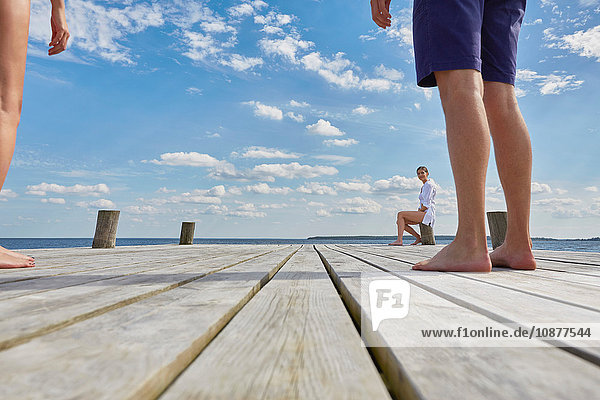 Young woman sitting on post on wooden pier  looking at friends standing further away