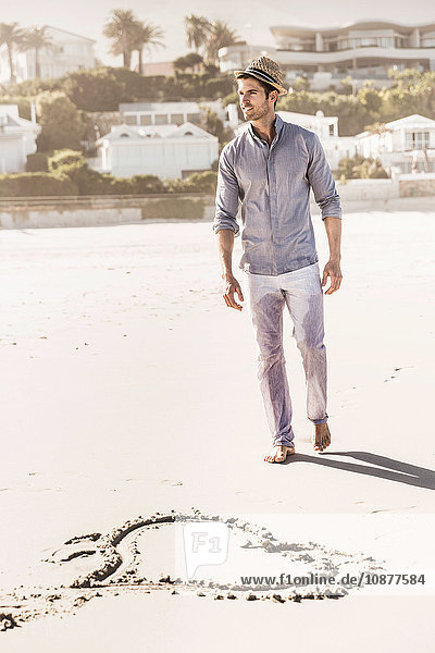 Heart shape in sand and young man strolling on beach  Cape Town  South Africa
