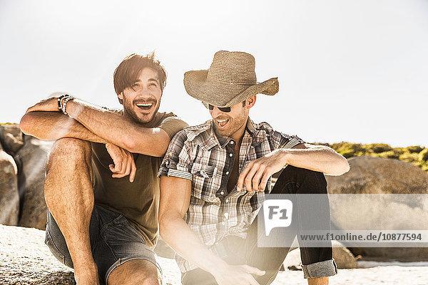 Zwei Männer lachend am Strand sitzend  Kapstadt  Südafrika