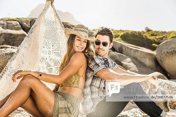 Paar sitzt Rücken an Rücken am Strand  Kapstadt  Südafrika