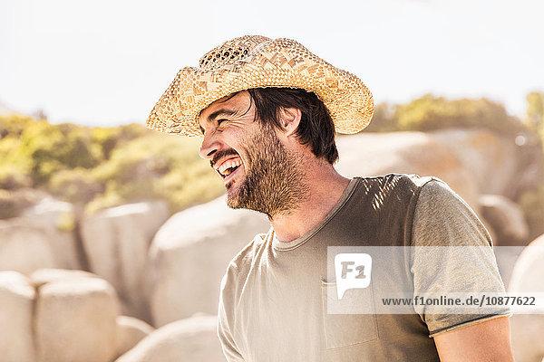 Glücklicher Mann mit Strohhut am Strand  Kapstadt  Südafrika