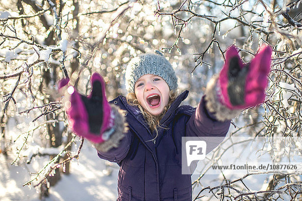 Young girl laughing  arms outstretched  in snowy landscape