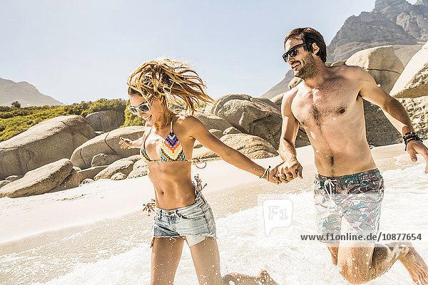 Paar in Badebekleidung läuft am Strand  Kapstadt  Südafrika