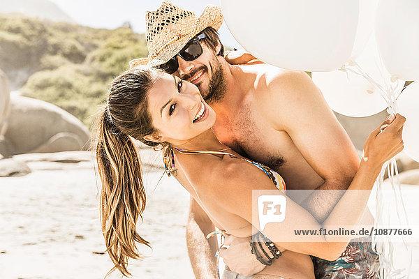 Porträt eines Paares mit einem Haufen Luftballons  die sich am Strand umarmen  Kapstadt  Südafrika