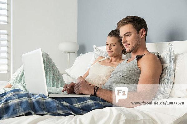 Junges Paar liegt im Bett und liest Buch und Laptop