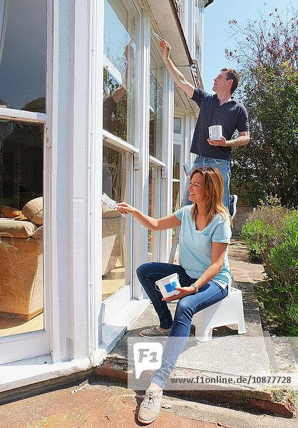 Couple painting window frame