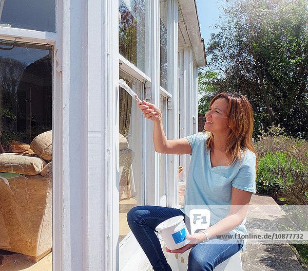 Frau malt Fensterrahmen