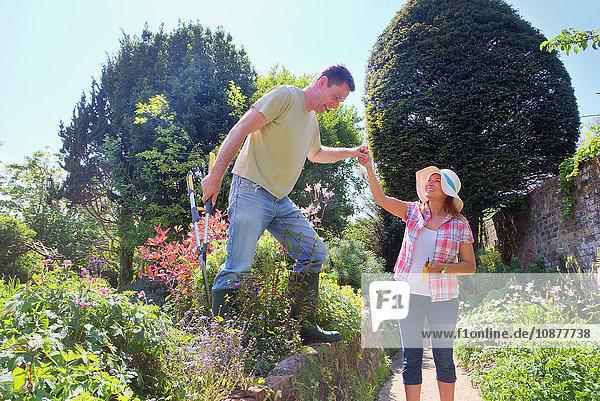 Frau im Garten hilft Mann beim Rücktritt von der Mauer