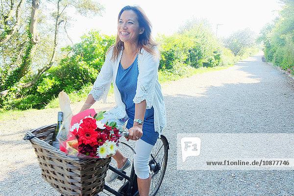 Frau auf Fahrrad schaut lächelnd weg
