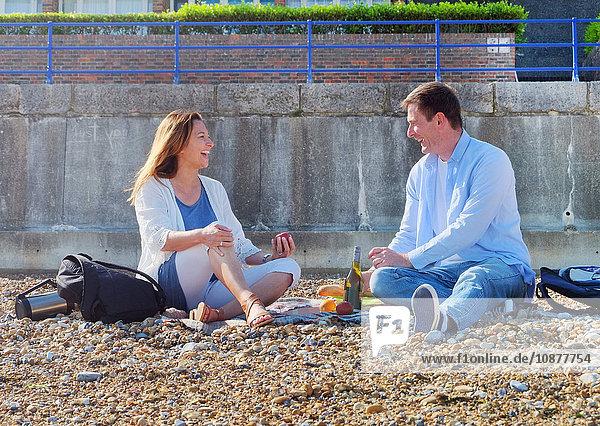Pärchen beim Picknick am Kiesstrand