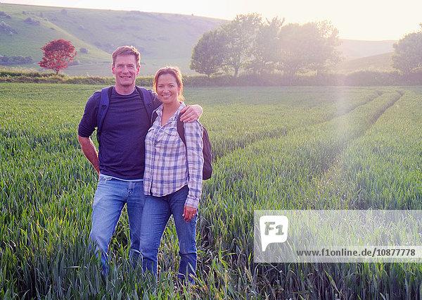 Paar im Feld schaut lächelnd in die Kamera