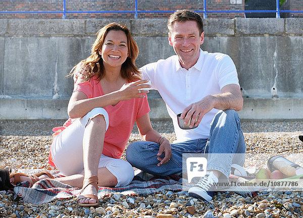Pärchen sitzt am Kiesstrand beim Picknick und schaut lächelnd in die Kamera