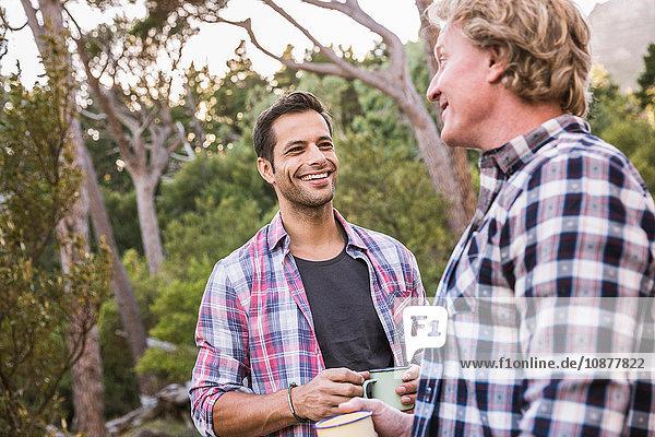 Zwei männliche Wanderer unterhalten sich bei Kaffee im Wald  Deer Park  Kapstadt  Südafrika
