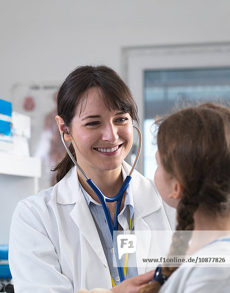 Female paediatric doctor listening to a young girl's chest with a stethoscope in a clinic