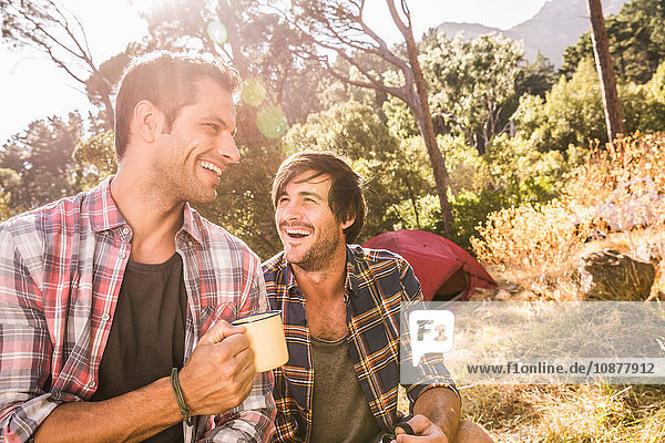 Two male campers chatting over coffee in forest  Deer Park  Cape Town  South Africa